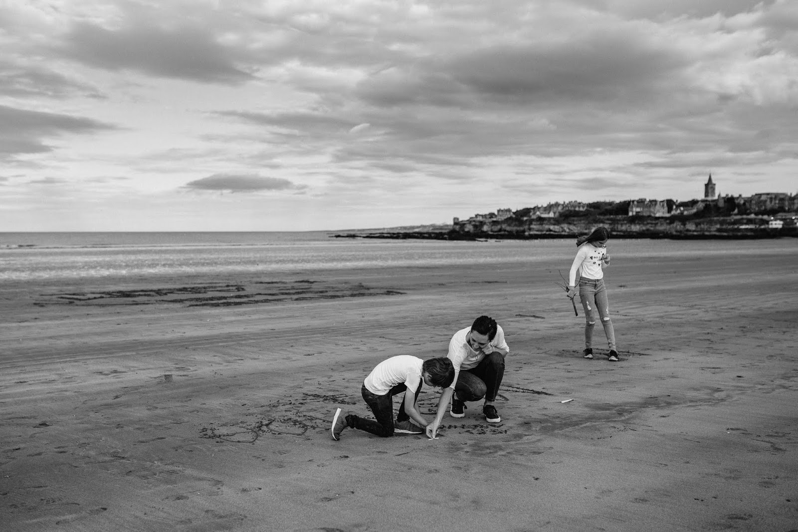 family drawing on sand West Sands beach with St Andrews in the background,