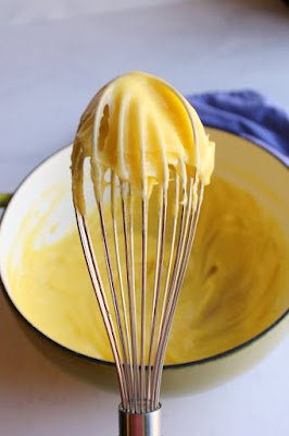 warm golden custard mixture on an inverted whisk