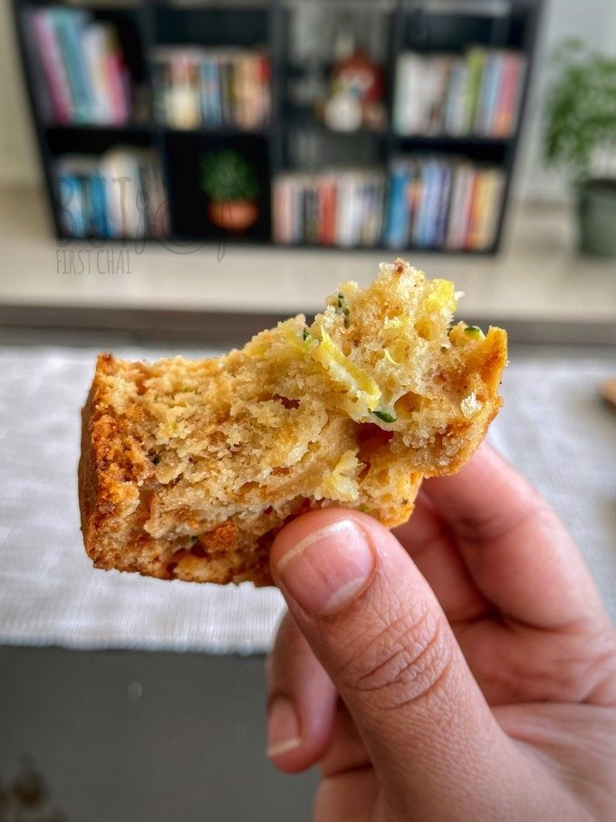 hand holding a small piece of zucchini bread half eaten