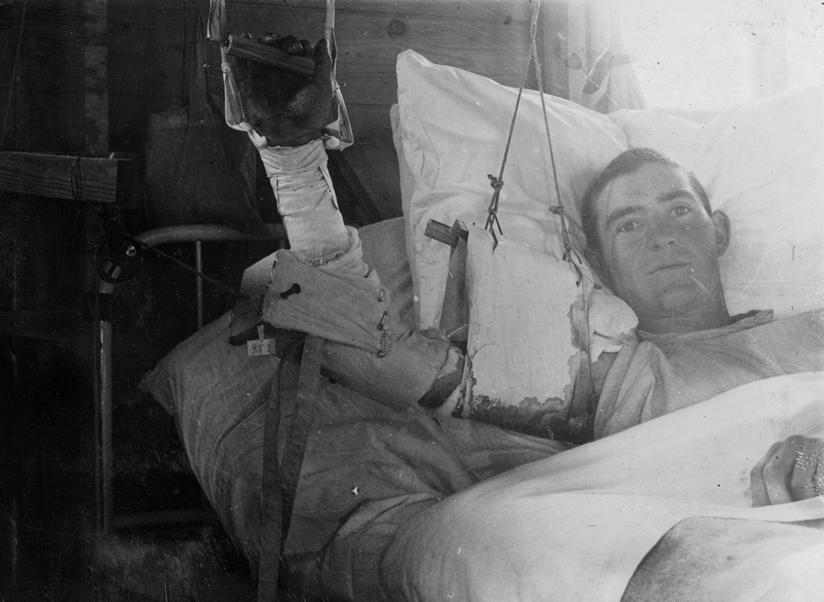 A wounded man recovers in a hospital bed.
