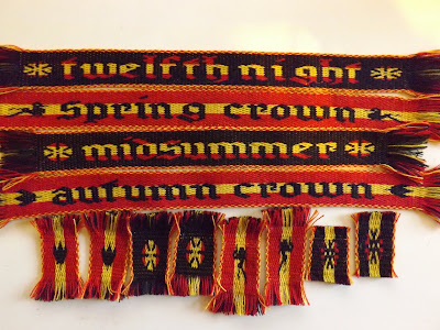 Tablet woven bands in black, red and yellow, woven with contrasting text