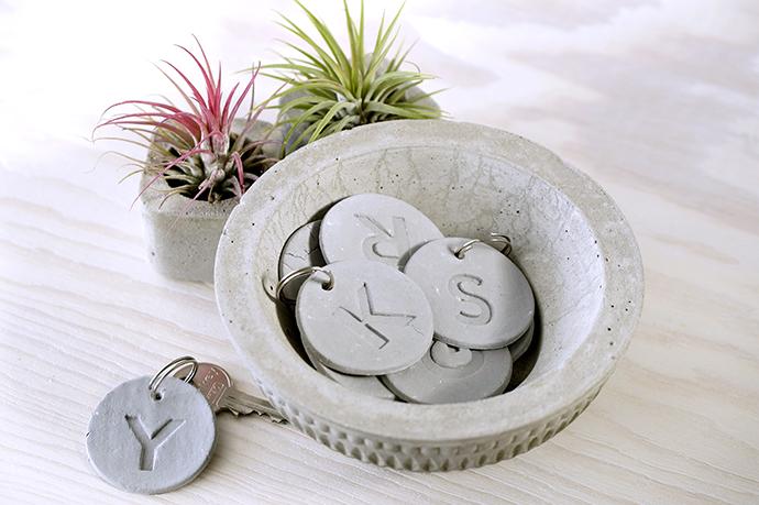 Kleine Scheiben aus Modelliermasse mit Buchstaben und Schlüsselring, 2 Aufsitzerpflanzen in Betonvasen