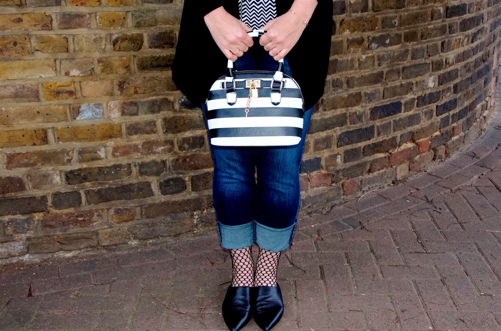 striped bag, fishnet socks, jeans and black leather slides
