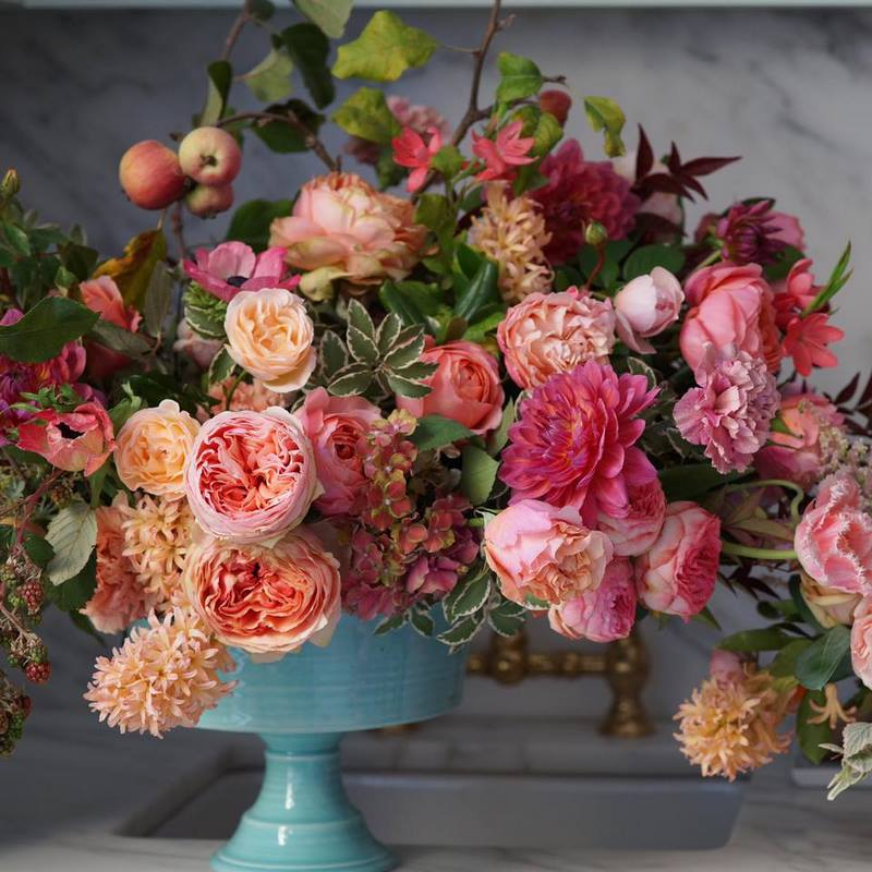 jarrón azul turquesa, flores y frutos