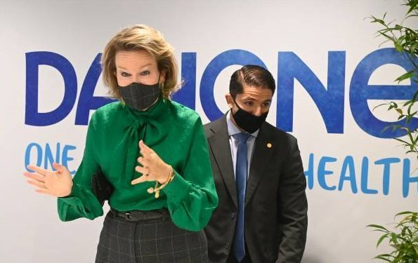Queen Mathilde wore a new green bow blouse from Carolina Herrera and grey check print trousers from Natan. She visited the facilitys of Danone