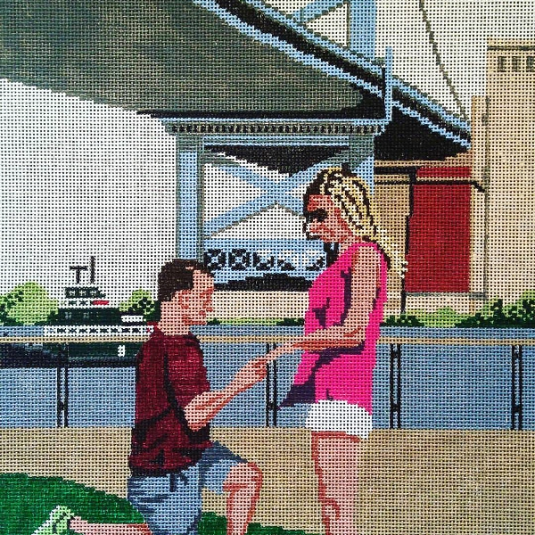 Needlepoint canvas of a man on one knee proposing to a woman under a suspension bridge