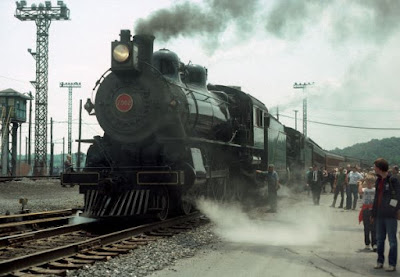 Large black steam locomotive with with people standing beside it