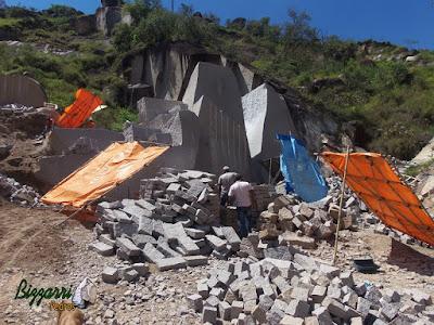 Extração de pedra de granito bruto sendo cortado para execução de pedra paralelepípedo.