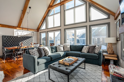 a brightly lit natural chalet interior with vaulted ceilings and a full wall of windows on a sunny winter day.