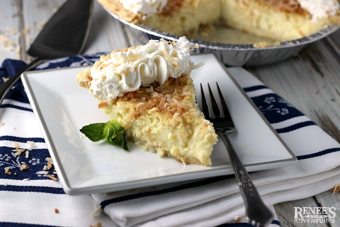 Coconut Custard Pie on white plate with fork and mint garnish
