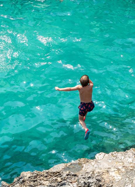 Niño saltando a un mar turquesa