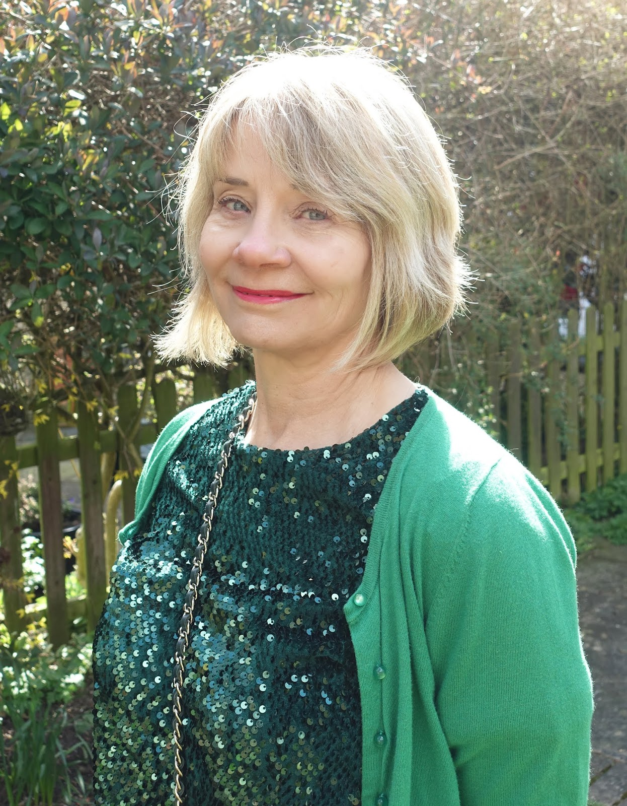 Portrait of mid life woman blonde hair in green sequin top