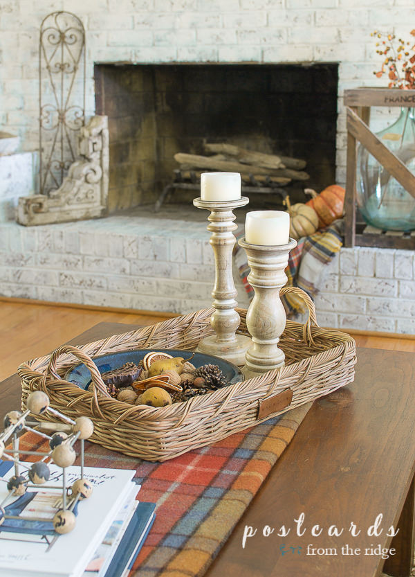 plaid blanket on a table with a basket of fall decor and wooden candlesticks