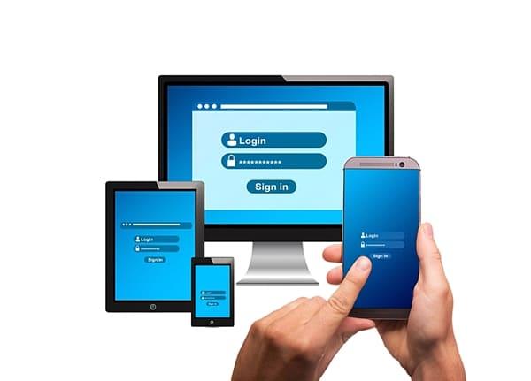 Mãos segurando smartphone com tela de login computador e tablet de fundo