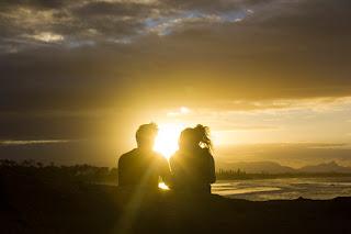 Imagen de una pareja sentada al atardecer en una playa