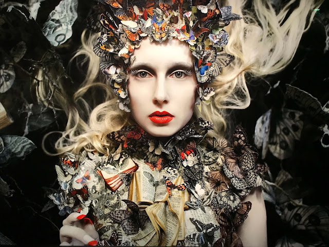 A fairy-tale blonde woman decorated with book pages and butterflies, wearing red lipstick and nailpolish.