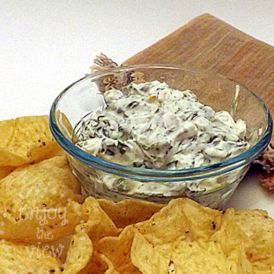 vegetable dip in a glass bowl surrounded by tortilla chips and a cloth napkin