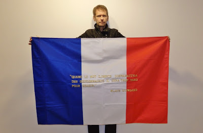 Klaus Guingand and his flag with the sentence in French.