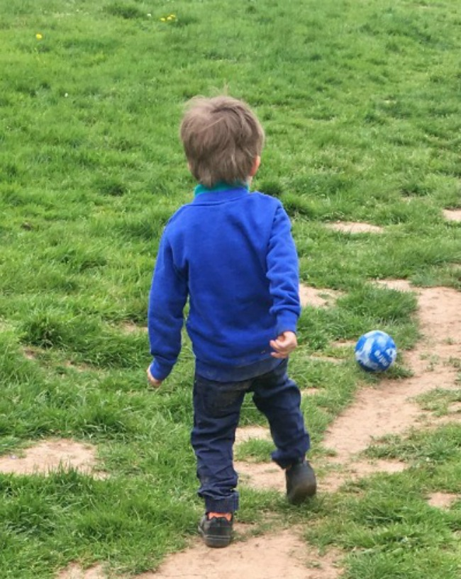 boy-playing-football-on-mud-and-grass