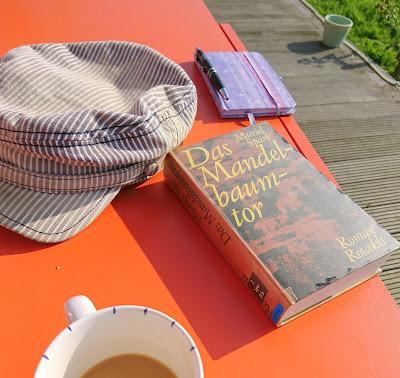 """Buch """"Das Mandelbaumtor"""" auf orangem Gartentisch mit Kaffee, Gartenmütze und Notizbuch"""