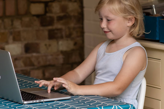 An online maths tutoring session is taking place with a laptop and a 5 year old girl