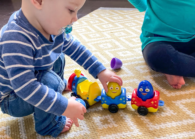 A baby taking a yellow egg with a smiling face out of a red, yellow and blue plastic toy train