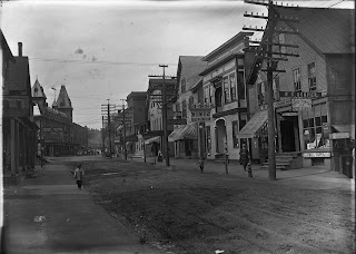A black and white photograph of a mostly empty street.