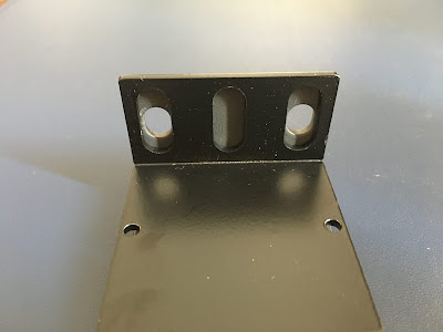 The 3-hole ear from the power strip's mounting plate