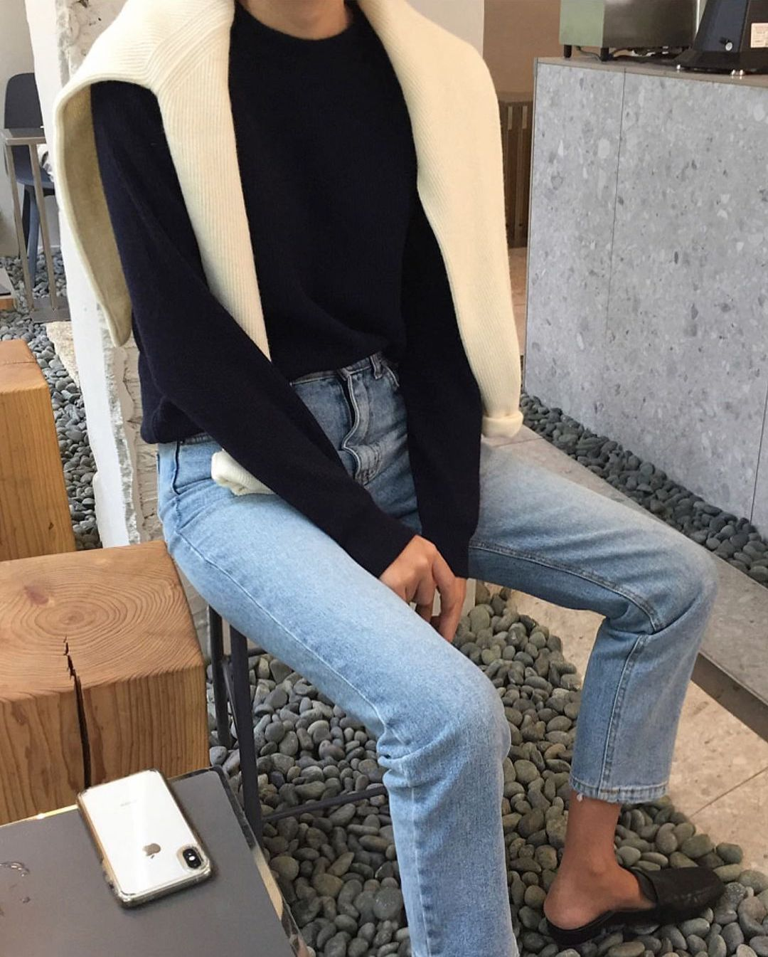 Effortless spring outfit idea from deathbyelocutionblog with a cream sweater over the shoulder, basic black sweater, straight-leg jeans, and mule loafers