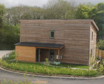 The North-facing rear of a three bedroomed eco-house. The homes are clad in local larch. This is projected to last at least 25 years before it needs replacing.