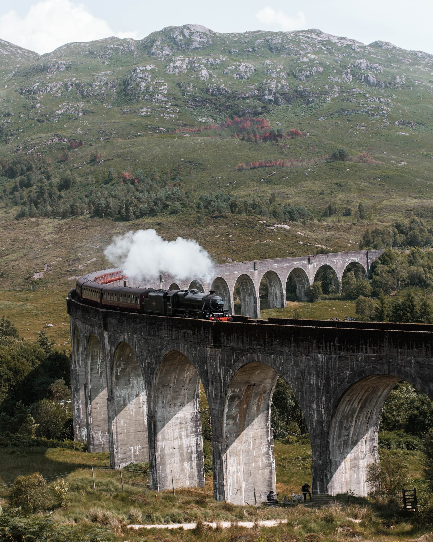 a photo of the hogwarts express from harry potter or the jacobite express steam train crossing glenfinnan viaduxt in the highlands of scotland