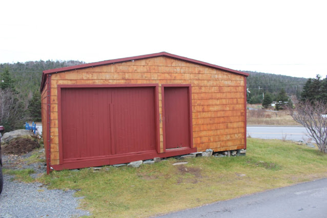 Photo of the Burgess Sawmill today. It is a short, long building, with an orange shingled exterior, a pair of wide garage doors painted red, and a regular door also painted red.