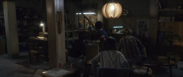 los niños estan en un sotano decorado y vemos una caja de pizza marca one y dos latas de coca cola