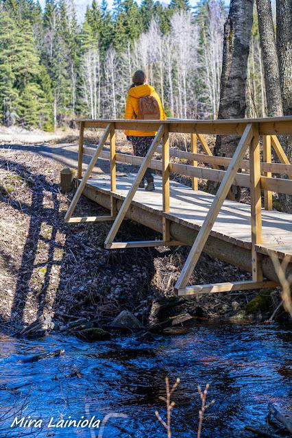 Nainen ylittää pienen puron siltaa pitkin