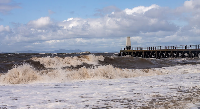 Photo of big waves whipped up by high winds crashing onto the shore at Maryport