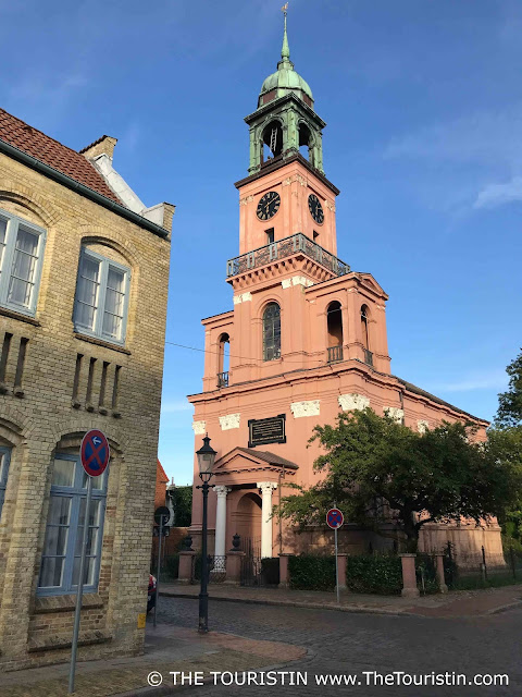 The pink Remonstrant Church in Friedrichstadt, under a blue sky