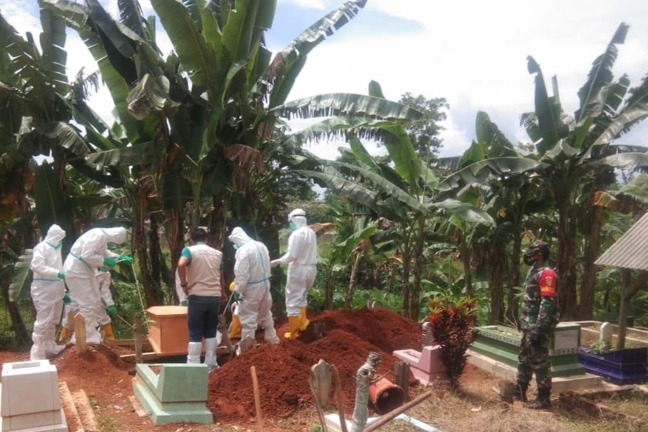 Babinsa Koramil 410-06/Kedaton Serka Agus Raharjo memonitor kegiatan pemakaman jenazah di TPU Way Kandis