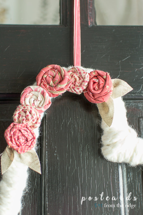 flowers made from fabric scraps and attached to a yarn wreath