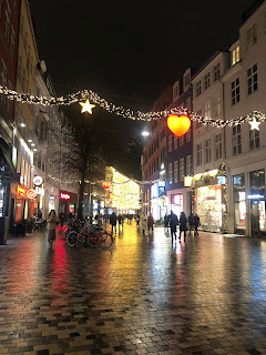 A holiday-lit street , wet with rain, with stores on either side.