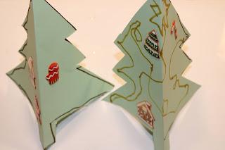 2 postais em forma de Árvore de Natal, decorados o do lado esquerdo com autocolantes e o do direito com marcadores e autocolantes