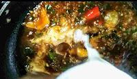 Pouring slurry over chilli chicken gravy