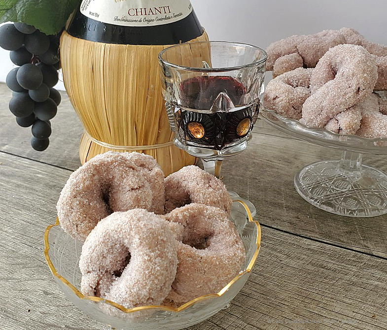 these are an round Italian cookie made with red wine and coated in sugar in a glass dish with a bottle of chianti and more cookies i n the background