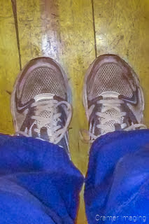 Unflattering photograph of two legs and tennis shoes on a wooden floor by Cramer Imaging