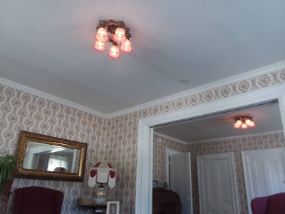 The double parlor with Victorian wallpaper and two new antique-styled chandeliers, each with five pink etched domes, visible