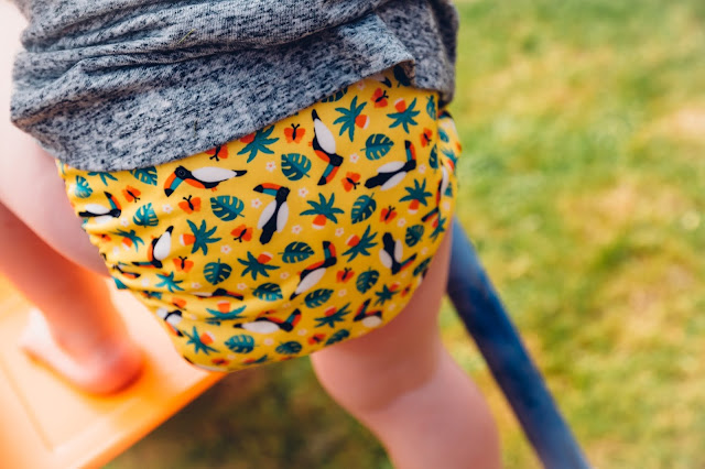 close up of a miosolo cloth nappy being worn by a toddler playing outdoors