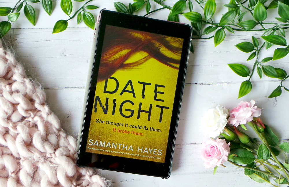 Kindle fire shows the cover of Date Night next to a pink chunky knit blanket, leaves and roses. The cover of Date Night is yellow with red hair spread across the top and the title written in black