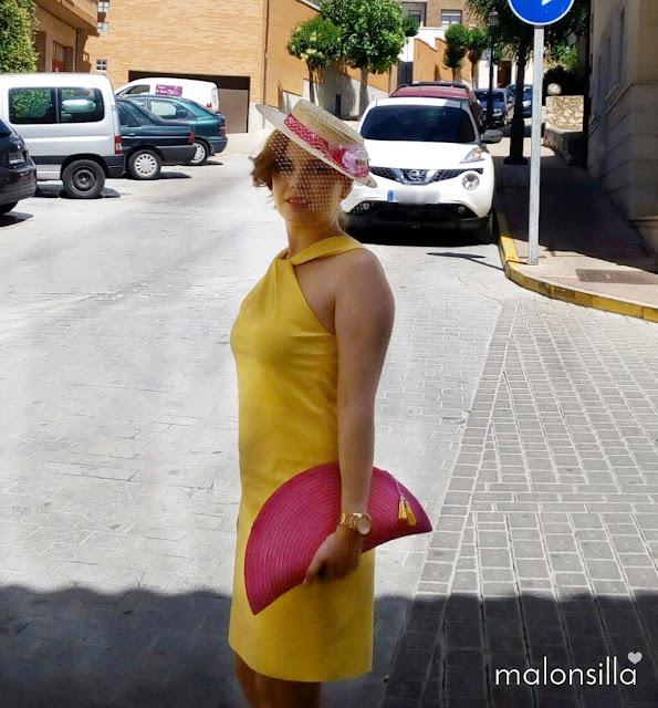 Invitada boda con vestido amarillo corto con escote en la espalda, canotier de flores de copa baja en fucsia y bolso abanico fucsia