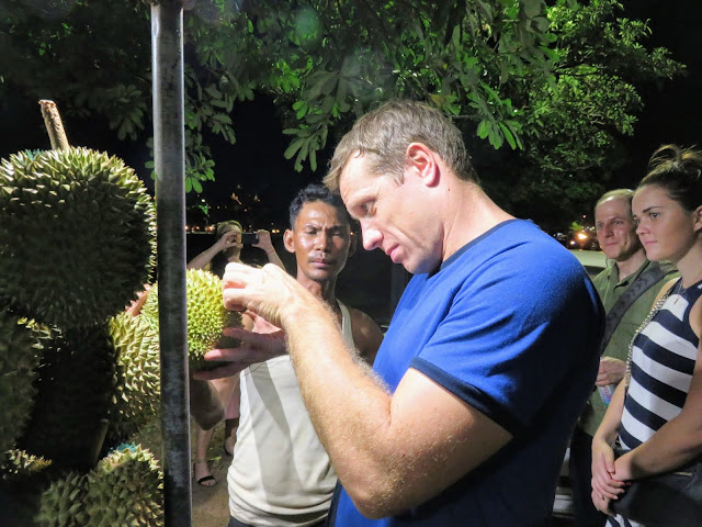 Steven from Siem Reap Food Tours selecting a durian