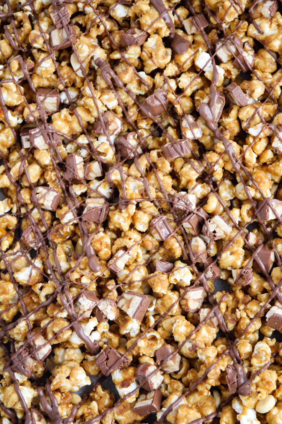 Snickers caramel popcorn - a delicious mix of crunchy caramel corn, peanuts, Snickers pieces, and chocolate. So addicting and delicious!