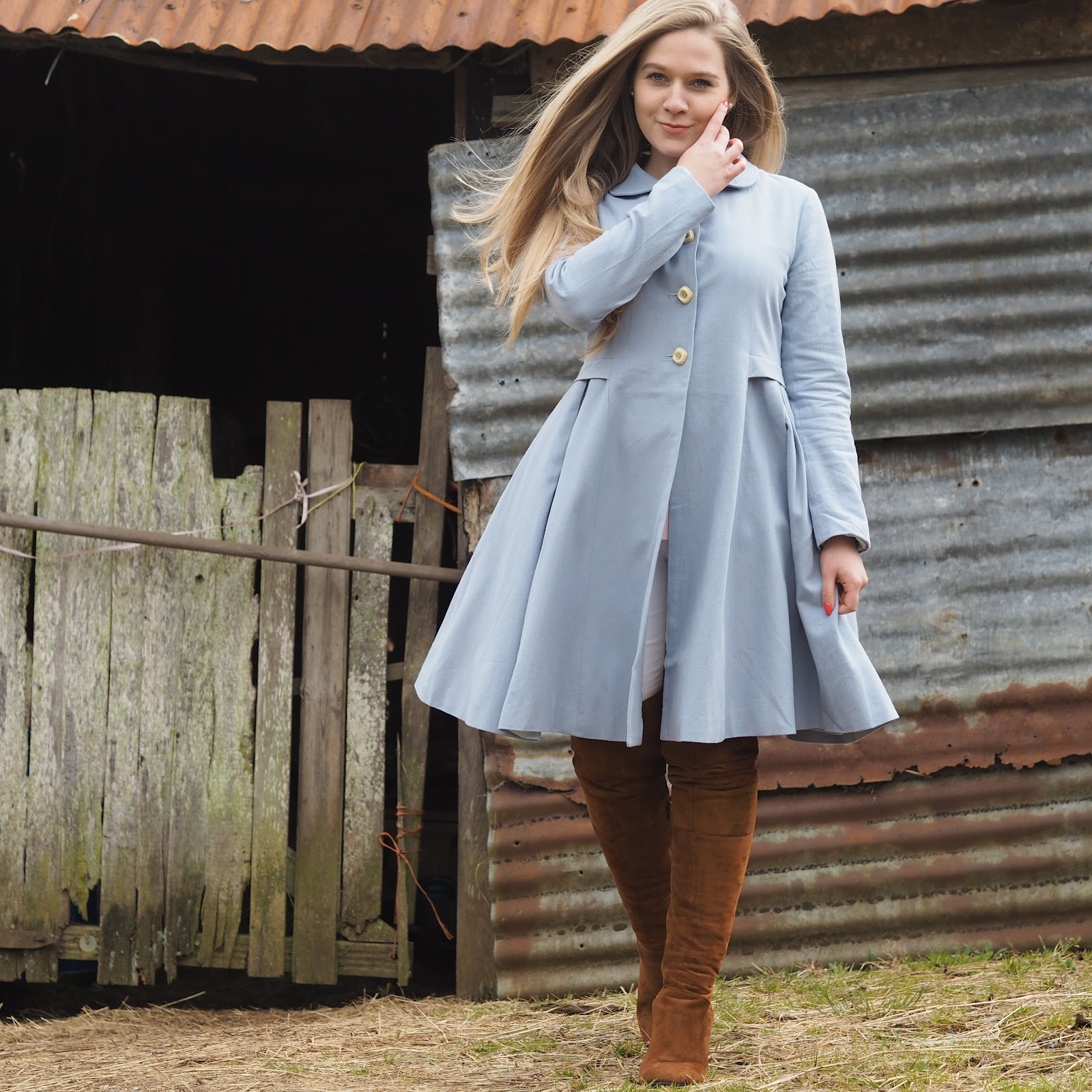 Blonde girl wearing blue coat and brown boots standing in front of old stables
